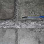 Spalling and faulting at a joint in an old concrete floor.  Damage like this can only occur at a slab edge.